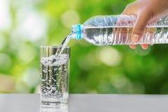 вручите лить питьевую воду в стеклянную бутылку формы на таблице с стоковое изображение rf