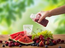Вручите лить фруктовый сок от бутылки к стеклу стоковая фотография rf