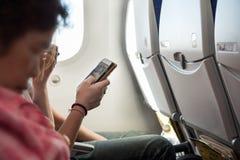Вручите мобильный телефон владением пока сидящ внутри самолета воздуха Стоковое фото RF