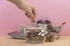 Вручите монетку денег сбережений в копилке на столе стоковая фотография rf