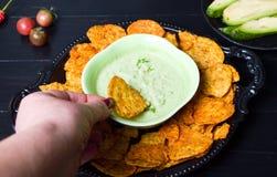 Вручите окунать обломоки tortilla в зеленое погружение стоковое фото rf