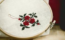 Вручите орнамент цветка вышивки крестиком вышивки на белой ткани Стоковые Фото