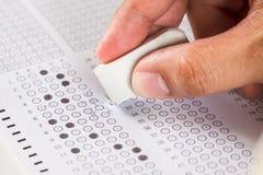 Вручите ответ неправды стирания на листе компьютера копировальной карбоновой бумаги экзамена Стоковая Фотография RF