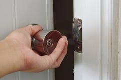 Вручите переплетать серебряную ручку к раскрытой двери в темной комнате Стоковая Фотография