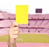 Вручите показывать желтую карточку перед стадионом стоковое фото rf