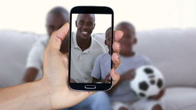 Вручите показывать зажимы футбола людей наблюдая на smartphone акции видеоматериалы