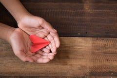 Вручите показывать или держать красный бумажный самолет на предпосылке деревянного стола Стоковое Изображение RF