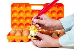 Вручите покрашенному цыпленку красную ручку цыпленка на предпосылке контейнера Стоковая Фотография RF