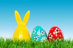 Вручите покрашенную игрушку пасхальных яя и кролика зайчика на траве Стоковые Изображения