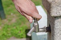 Вручите потек воды отверстия от водопроводного крана в парке Стоковые Фото