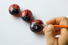 Вручите при щетка крася 3 камня как ladybugs Стоковое Фото