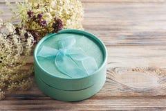 Вручите произведенный минимальный зеленый подарок с смычком, цветком Стоковое Изображение RF