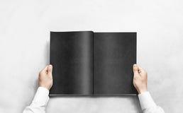 Вручите раскрывая черный журнал с модель-макетом пустых страниц Стоковые Изображения