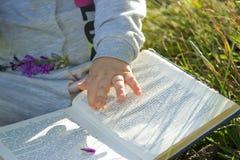 Вручите ребенк на книге стоковые изображения rf
