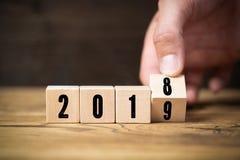 Вручите слегка ударять куб, symbolizng изменение от 2018 до 2019 стоковая фотография