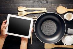 Вручите таблетку пользы с kitchenware на черной деревянной таблице, море концепции Стоковое фото RF