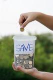 Вручите установку монетки в опарник стоковые изображения