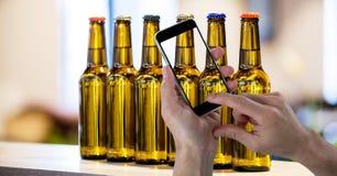 Вручите фотографировать пивные бутылки через умный телефон Стоковые Изображения