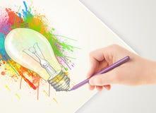 Вручите чертежу на бумаге красочную лампочку splatter Стоковые Фото
