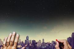 Вручите чертеж на классн классном, с панорамным видом на город с небом и звездами на предпосылке ночи Стоковое фото RF