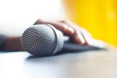 Вручите человеку ` s касающий микрофон на предпосылке цвета Стоковое Изображение RF
