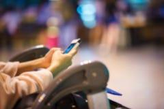 Вручите экран владением и касанием умные телефон и вагонетка авиапорта, дальше Стоковая Фотография RF