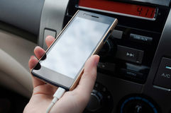 Вручите smartphone владением в автомобиле, телефоне штепсельной вилки заряжателя на автомобиле Стоковые Изображения RF