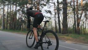 Всадник велосипеда sprinting из седловины как парк задействуя тренировки Нося черное обмундирование Сильные мышцы ноги сток-видео
