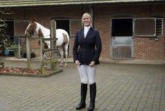Всадник лошади женщины стоя в стабилизированном дворе Стоковое Фото