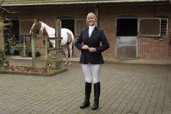 Всадник лошади женщины стоя в стабилизированном дворе Стоковая Фотография RF