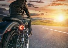 Всадник мотоцикла готовый для привода в Альпах, красивого неба захода солнца стоковое фото