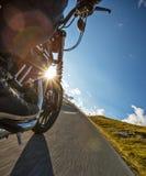 Всадник мотоцикла управляя в Альпах Стоковые Изображения