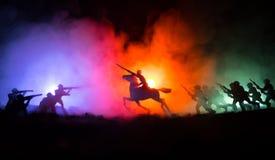 Всадник офицера мировой войны (или ратника) на лошади с шпагой готовой для боя и солдатами на темной туманной тонизированной пред стоковое фото rf
