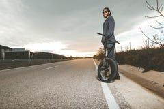 Всадник BMX делая фокусы Молодой человек с велосипедом bmx весьма спорты стоковая фотография
