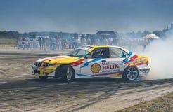 Всадник v Borovitsky на BMW бренда автомобиля преодолевает след Стоковое Изображение