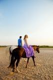 2 всадника верхом на заходе солнца на пляже Hors езды любовников Стоковое Изображение RF