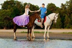 2 всадника верхом на заходе солнца на пляже Hors езды любовников Стоковые Фото