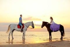 2 всадника верхом на заходе солнца на пляже Hors езды любовников Стоковая Фотография