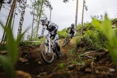 2 всадника спортсмена на велосипеде вниз через древесины от горы Стоковые Изображения RF