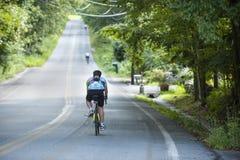 Всадники зашнурованные вне вдоль дороги в длинной езде велосипеда для призрения Стоковое Изображение RF