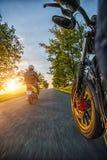 Всадники мотоцилк управляя к красивому заходу солнца освещают на пустой Стоковое Изображение RF