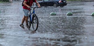 Всадник велосипеда в ненастном городе Стоковое Изображение