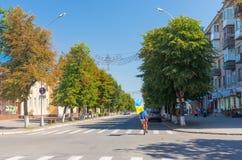 Всадник велосипеда задействуя с украинским флагом на улице главного города Стоковое Фото