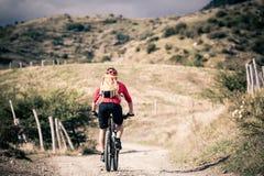 Всадник горного велосипеда на проселочной дороге, следе следа в inspirationa Стоковые Фотографии RF