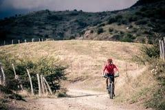 Всадник горного велосипеда на проселочной дороге, следе следа в inspirationa Стоковые Фото