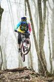 Всадник горного велосипеда скачет от трамплина в туманном лесе, в горах Кавказа Стоковое Изображение