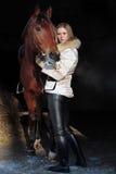 Всадник девушки около ее коричневой лошади в конюшне получает готовым Стоковые Изображения
