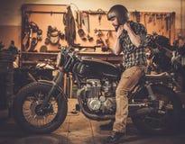 Всадник и его винтажный мотоцикл каф-гонщика стиля Стоковое Фото