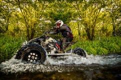 Всадник квада через поток воды Стоковое Изображение