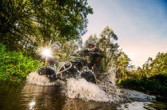 Всадник квада через поток воды Стоковые Изображения RF